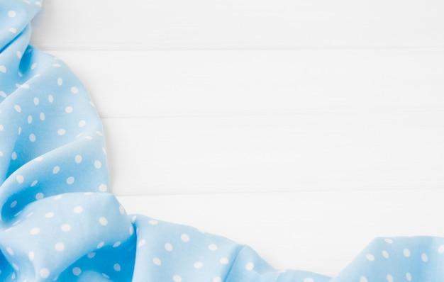 표백 나무 테이블 위에 밝은 파란색 폴카 도트 접힌 식탁보.