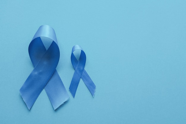 Light blue ribbons on blue background , prostate cancer  men health awareness