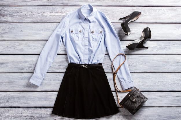 水色のシャツとかかと。かかとの靴と黒いスカート。財布とカジュアルな夜の服装。ストラップ付きの女性のクラシックバッグ。