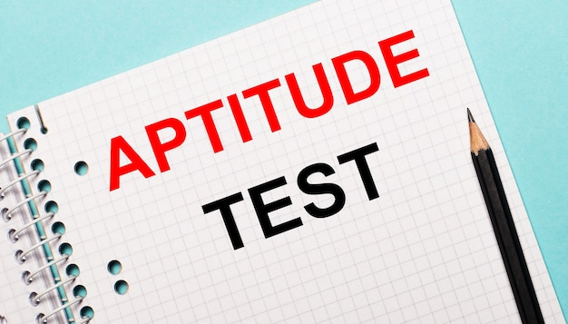 On a light blue surface, a checkered notebook with the words aptitude test and a black pencil