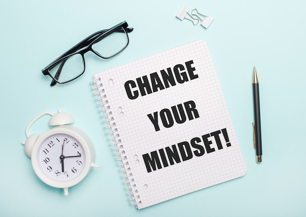 On a light blue surface lie black glasses and a pen, a white alarm clock, white paper clips and a notebook with the words change your mindset