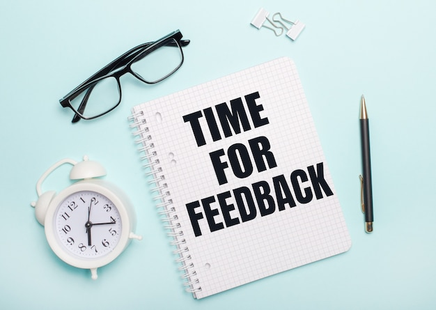 On a light blue surface lie black glasses and a pen, a white alarm clock, white paper clips and a notebook with the words time for feedback. business concept