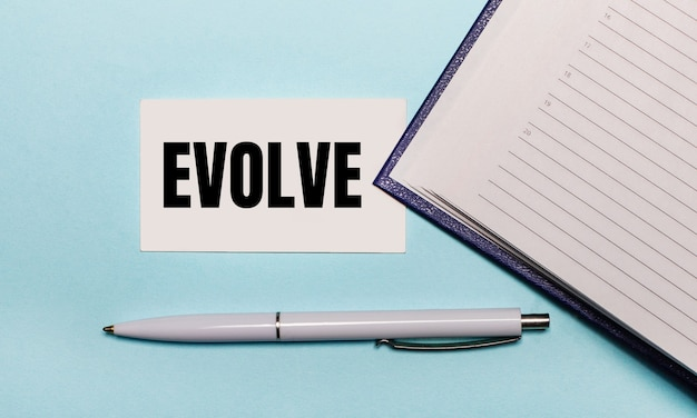 On a light blue surface, an open notebook, a white pen and a card with the text evolve