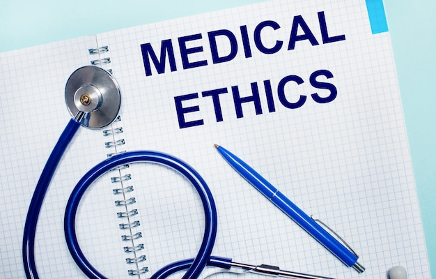 On a light blue surface, an open notebook with the words medical ethics, a blue pen and a stethoscope