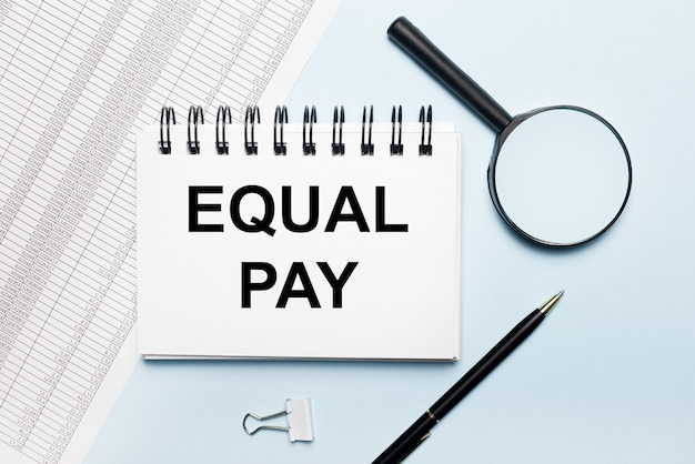 On a light blue surface, reports, a magnifying glass, a pen and a notebook with the text equal pay