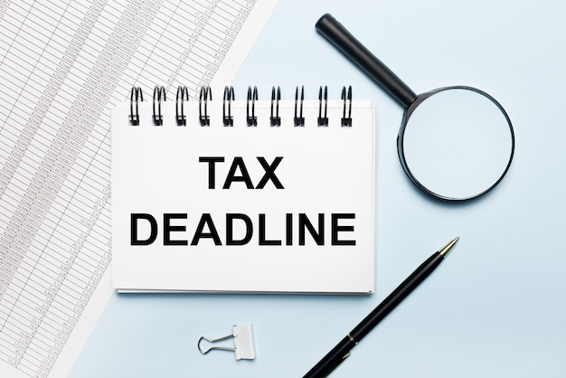 On a light blue surface, reports, a magnifying glass, a pen and a notebook with the text tax deadline