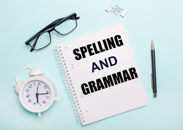 On a light blue table lie black glasses and a pen, a white alarm clock, white paper clips and a notebook with the words spelling and grammar. business concept