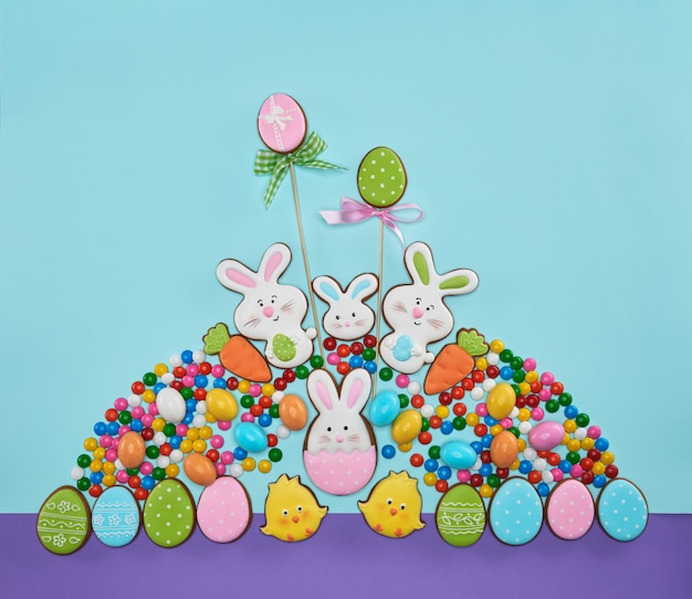 Light blue and violet background with sweets in shape of egg, bunny and chicken.