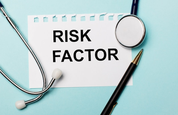 On a light blue wall, a stethoscope, a pen and a sheet of paper with the inscription risk factor. medical concept