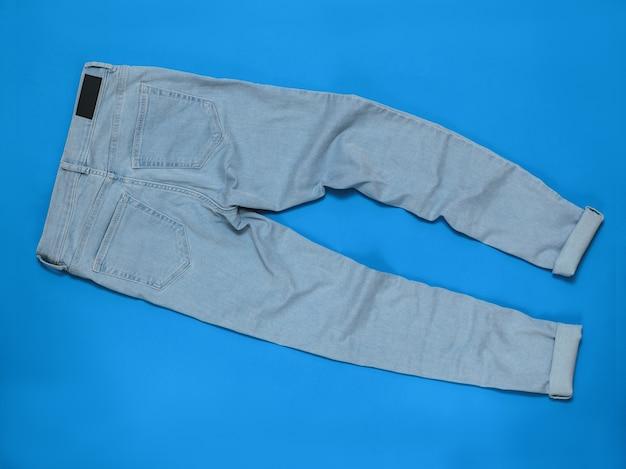 Голубые женские джинсы. понятие современной моды на электронные устройства. плоская планировка. вид сверху.