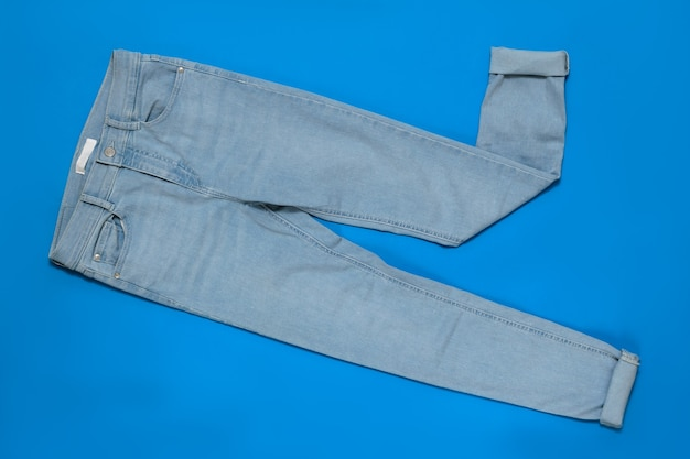 Light blue women jeans with cuffs on blue background. the concept of modern fashion for electronic devices. flat lay. the view from the top.