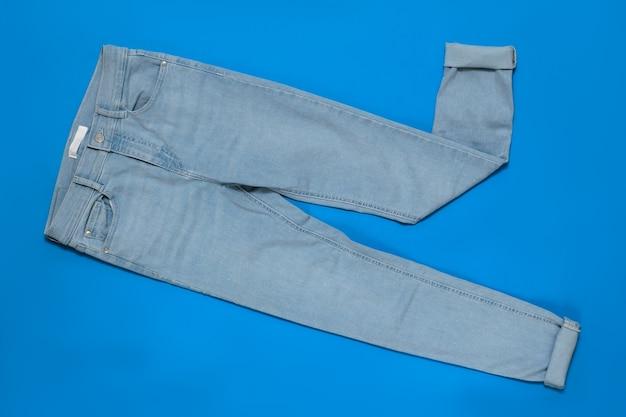 青い背景に袖口のある水色の女性のジーンズ。電子機器の現代ファッションの概念。フラットレイ。上からの眺め。