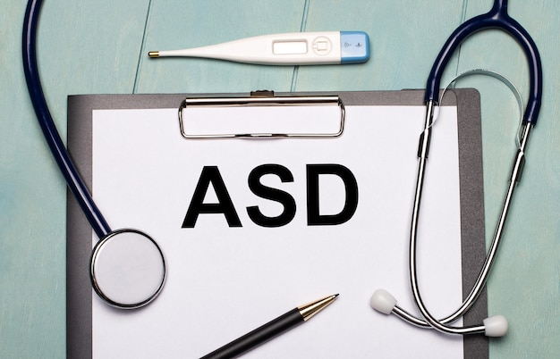 On a light blue wooden background, there is a paper labeled asd autism spectrum disorder, a stethoscope, an electronic thermometer, and a pen. medical concept