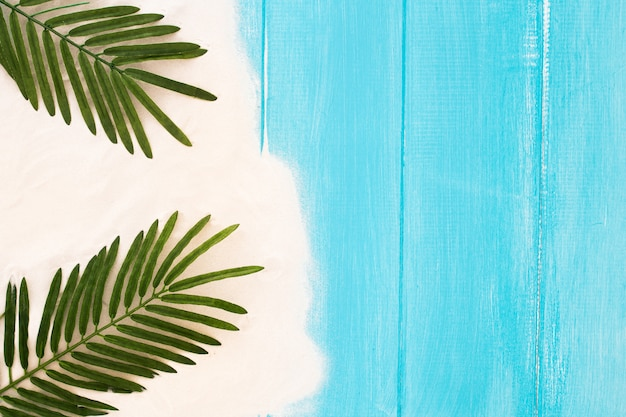 Light blue wooden background with sand and palm leaf, summer background