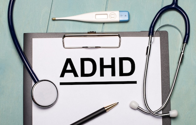 On a light blue wooden surface, there is a paper labeled adhd, a stethoscope, an electronic thermometer, and a pen