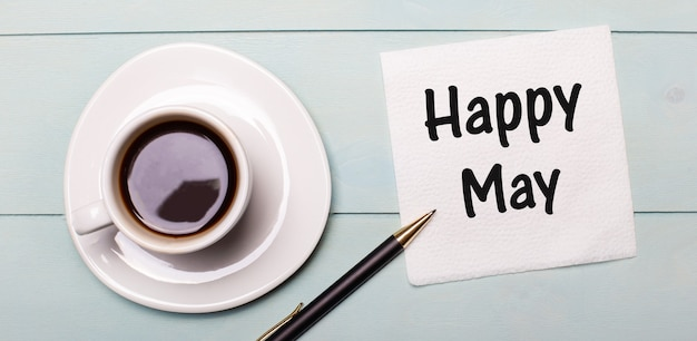 On a light blue wooden tray, there is a white cup of coffee, a handle and a napkin that says happy may
