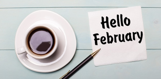 On a light blue wooden tray, there is a white cup of coffee, a handle and a napkin that says hello february