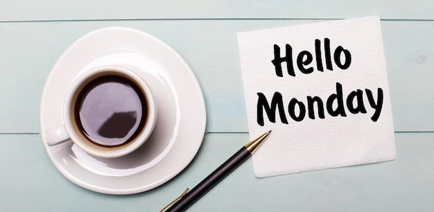 On a light blue wooden tray, there is a white cup of coffee, a handle and a napkin that says hello monday.