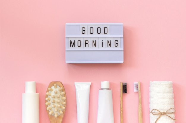 Light box text good morning and set of cosmetics products and tools for shower or bath on pink background