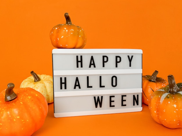 Light box with happy halloween phrase with pumpkins decoration on an orange background.