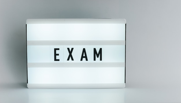 Light box with the headline exam with copyspace, over white background