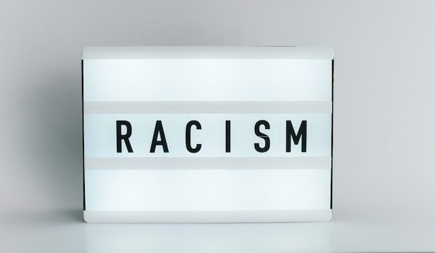Light box with the headline racism with copyspace, over white background