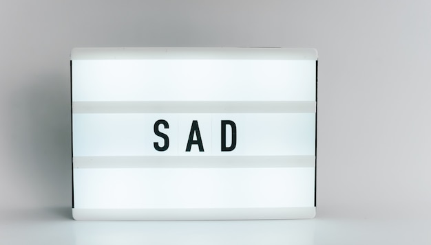 Light box with the headline sad with copyspace, over white background