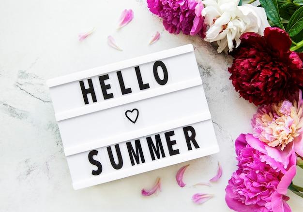 대리석 표면에 안녕하세요 여름 텍스트와 모란 꽃이있는 라이트 박스