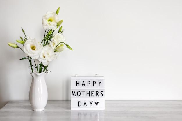 幸せな母の日をレタリングしたライトボックス、コピースペースのある白い木製のテーブルの上に花瓶に白い花のトルコギキョウまたはトルコギキョウ。