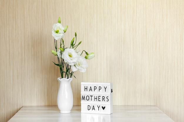 幸せな母の日をレタリングしたライトボックス、コピースペースのある木製のテーブルの上に花瓶に白い花のトルコギキョウまたはトルコギキョウ。