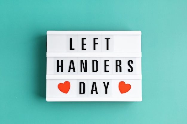 Light box with text left handers day and hearts over blue background