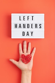 Light box with text left handers day and left palm with heart over orange background