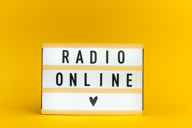 Light box with text, radio online, on yellow wall