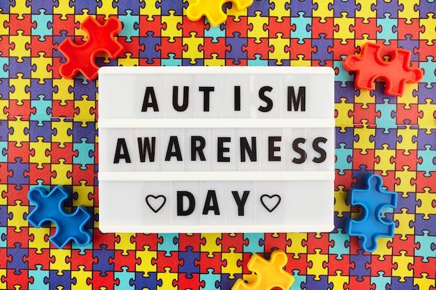 컬러 퍼즐 배경에 세계 자폐증 인식의 날 텍스트가있는 라이트 박스. 평면도