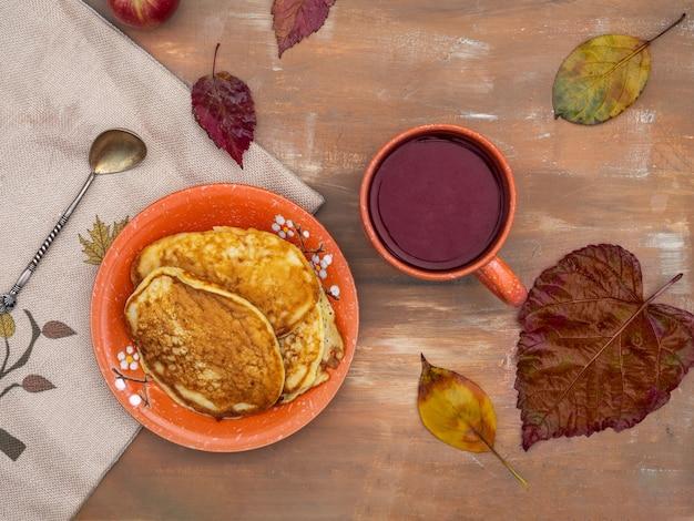 葉のある秋の庭での軽い朝食。ズッキーニのパンケーキとお茶