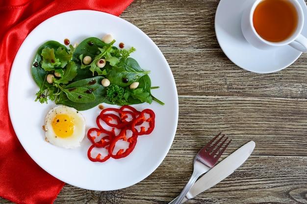 Легкий завтрак - перепелиное яйцо, зеленый салат, сладкий перец и чашка чая на деревянном столе. вид сверху. здоровая пища. правильное питание.