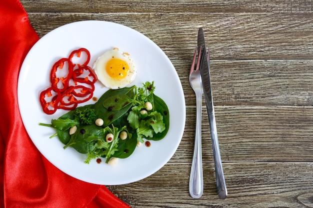 Легкий завтрак - перепелиное яйцо, зеленый салат, сладкий перец на деревянном столе. вид сверху. здоровая пища. правильное питание.
