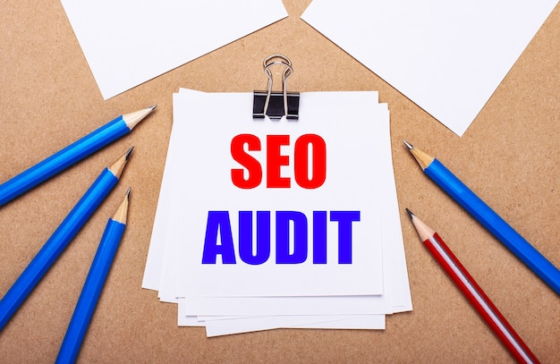 On a light brown background, blue and red pencils and white paper with the text seo audit