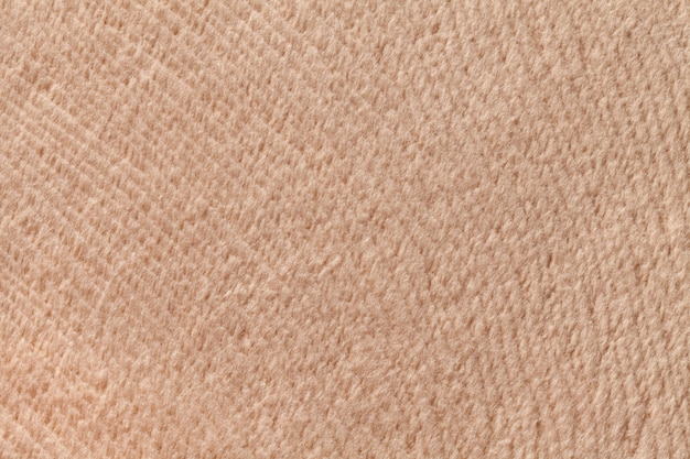 Light brown background from soft textile material. fabric with natural texture.