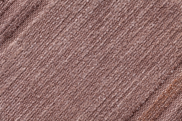 Light brown background of a knitted textile material. fabric with a striped texture closeup.
