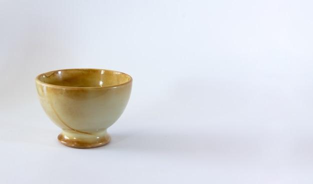 흰색 바탕에 니스를 칠한 밝은 갈색 세라믹 그릇. 선택적 초점입니다. 공간을 복사합니다.