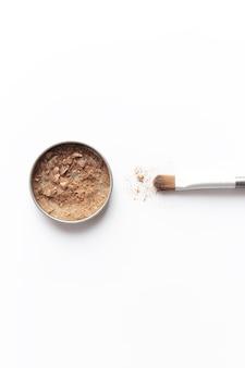 Светло-коричневые тени для лица в контейнере и тени для век или кисть для макияжа