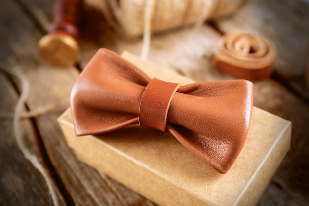 Light-brown leather bow tie and cardboard gift box on wooden table, close up