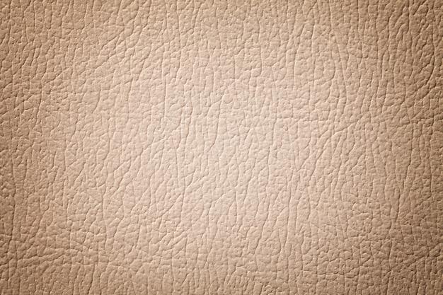밝은 갈색 가죽 질감 배경입니다. 베이지 색 금이 간, 비 네트가있는 섬유 구조.