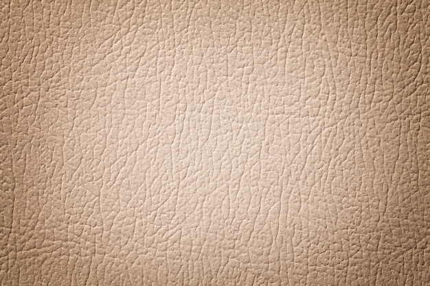 Light brown leather texture background. beige cracked, structure of textile with vignette.