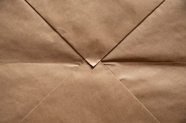 Light brown paper background in the form of craft envelope.