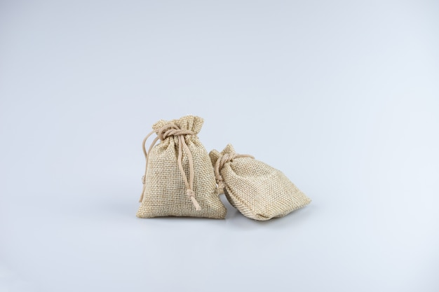Light brown sack bags on white background. filled with stuffs.
