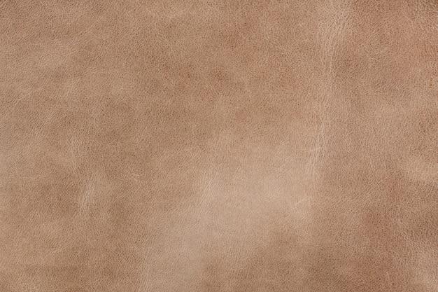 小粒の織り目加工の背景に明るい茶色の滑らかな天然皮革