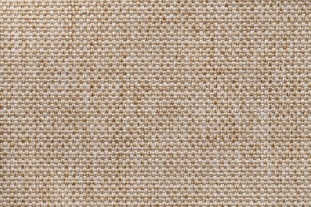 Light brown textile background closeup. structure of the fabric macro