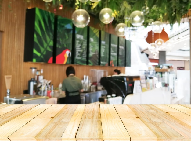 Light brown wooden board empty table on front with counter cashier in cafe